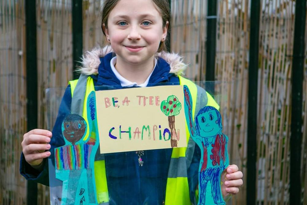 student holding be a tree champion sign - small